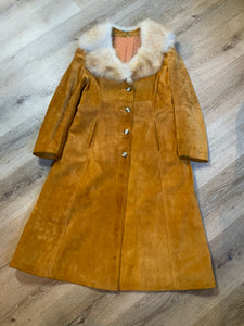 Embassy 1970's full length tan suede coat with fur collar, button closures, pockets and a salmon coloured quilted lining. Made in Montreal, Canada. Fits Small.