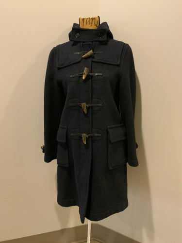 Gloverall navy blue wool duffle coat with hood, zipper, wooden toggles, flap pockets and green plaid lining. Made in England.