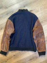Load image into Gallery viewer, Ford F-Series 50 year anniversary letterman's jacket in navy with brown leather sleeves, snap closures, slash pockets and an inside pocket.