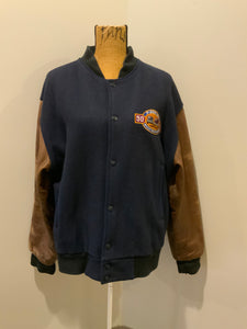 Ford F-Series 50 year anniversary letterman's jacket in navy with brown leather sleeves, snap closures, slash pockets and an inside pocket.
