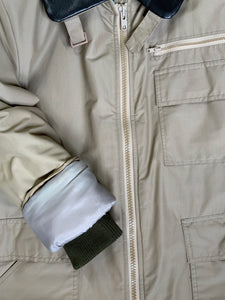 Kingspier Vintage - Special Reserve hunting jacket in beige with brown leather collar featuring a strap to keep your collar in place, zipper, three flap pockets and one zip pocket. Knit inside cuffs. lined for cooler weather with drawstring at waist. Made in Canada. Size 44.
