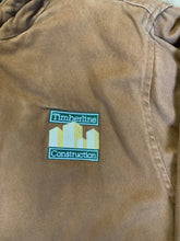 "Load image into Gallery viewer, Charles River tan canvas work jacket with slash pockets, patch pockets, hood, "" timberline construction"" embroidered emblem and quilted lining with inside pockets."