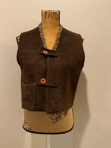 Brown sheepskin vest with two wooden button closures, one patch pocket and a knit mohair collar.