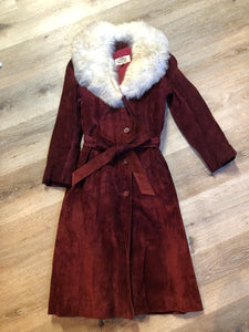 Leather Attic 1970's oxblood suede coat with fur collar. Beautifully fitted, the coat features pockets, buttons, a belt and a quilted lining. Made in Canada. Size small.
