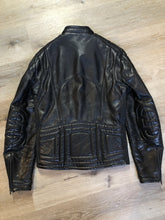 Load image into Gallery viewer, Taurus by Drospo black leather moto jacket with stretch detailing on the sides and a belt at the waist, zipper down the front, standing collar with Velcro strap, slash pockets and a quilted lining with inside pocket. Size 38. Made in Canada.