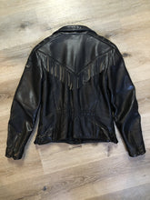 Load image into Gallery viewer, Hein Gericks black leather motorcycle jacket with fringe detail, zipper, vertical zip pockets lace-up shoulder detail, a quilted lining with inside pocket. Fits Small.