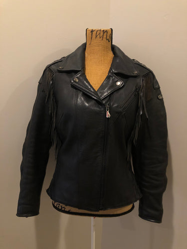 Kingspier Vintage - Hein Gericks black leather motorcycle jacket with fringe detail, zipper, vertical zip pockets lace-up shoulder detail, a quilted lining with inside pocket. Fits Small.