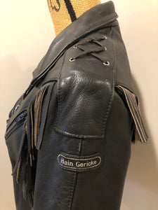 Hein Gericks black leather motorcycle jacket with fringe detail, zipper, vertical zip pockets lace-up shoulder detail, a quilted lining with inside pocket. Fits Small.