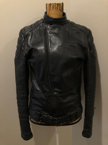 Kingspier Vintage - Taurus by Drospo black leather moto jacket with stretch detailing on the sides and a belt at the waist, zipper down the front, standing collar with Velcro strap, slash pockets and a quilted lining with inside pocket. Size 38. Made in Canada.