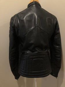 Taurus by Drospo black leather moto jacket with stretch detailing on the sides and a belt at the waist, zipper down the front, standing collar with Velcro strap, slash pockets and a quilted lining with inside pocket. Size 38. Made in Canada.