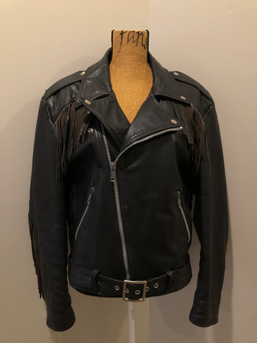 Kingspier Vintage - Action black leather motorcycle jacket with fringe detail and belt at waist. Zipper closure and zip slash pockets, quilted lining with inside pocket. Made in Canada. Size 40.