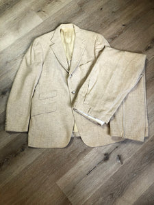 Chaps by Ralph Lauren light beige two piece suit sold at Martini Carl Boston. Jacket is a three button notch lapel with three flap pockets and a breast pocket. The pants are flat front with two slash pockets, a tiny flap pocket in the front and two back pockets.