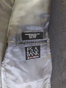 JoS. A. Bank, Signature Collection dark grey 100% wool two piece suit. Made in Mexico. Jacket is a three button notch lapel with two flap pockets and a breast pocket, three inside pockets and one coin pocket. Pants are pleated and cuffed with welt pockets in front and back and suspender buttons.