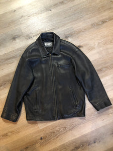 Roots black pebbled leather jacket with two vertical zip pockets and one zip pocket on the chest. Made in Canada. Size medium.