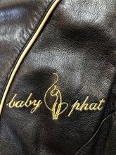 "Load image into Gallery viewer, Kingspier Vintage - Baby Phat black leather moto jacket with gold piping and ""Baby Phat"" embroidered on the chest, front zipper and two vertical zip pockets. A pattern is stitched into the elbows and ""Baby Phat"" is stitched across the back. Size small."