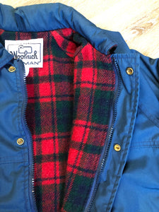 Kingspier Vintage - Woolrich Woman navy jacket with raglan sleeves, hood, zipper, snap closures with sheep logo, two flap pockets, drawstring at waist and red plaid wool lining. Made in the USA. Size medium.