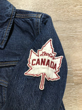Load image into Gallery viewer, Levi's Original Trucker Jacket in a medium wash denim with Canada leaf patch on the left shoulder, button closures, two vertical pockets and two flap pockets on the chest. Size XS.