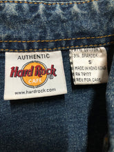 "Load image into Gallery viewer, Hard Rock Cafe denim work shirt style jacket in a ""dirty wash"" with snap closures, flap pockets, ""Hard Rock Cafe"" is stitched above the pocket and ""Chicago"" is stitched on the cuff. Size small."