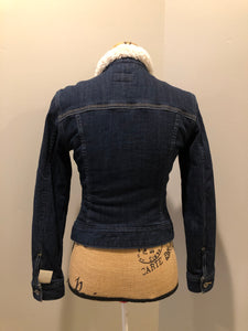 Levi's Sherpa style denim jacket in a dark wash with stretch, pleats running down the front, faux fur lining and quilted lining in both arms, button closures and one patch pocket. Size XS.