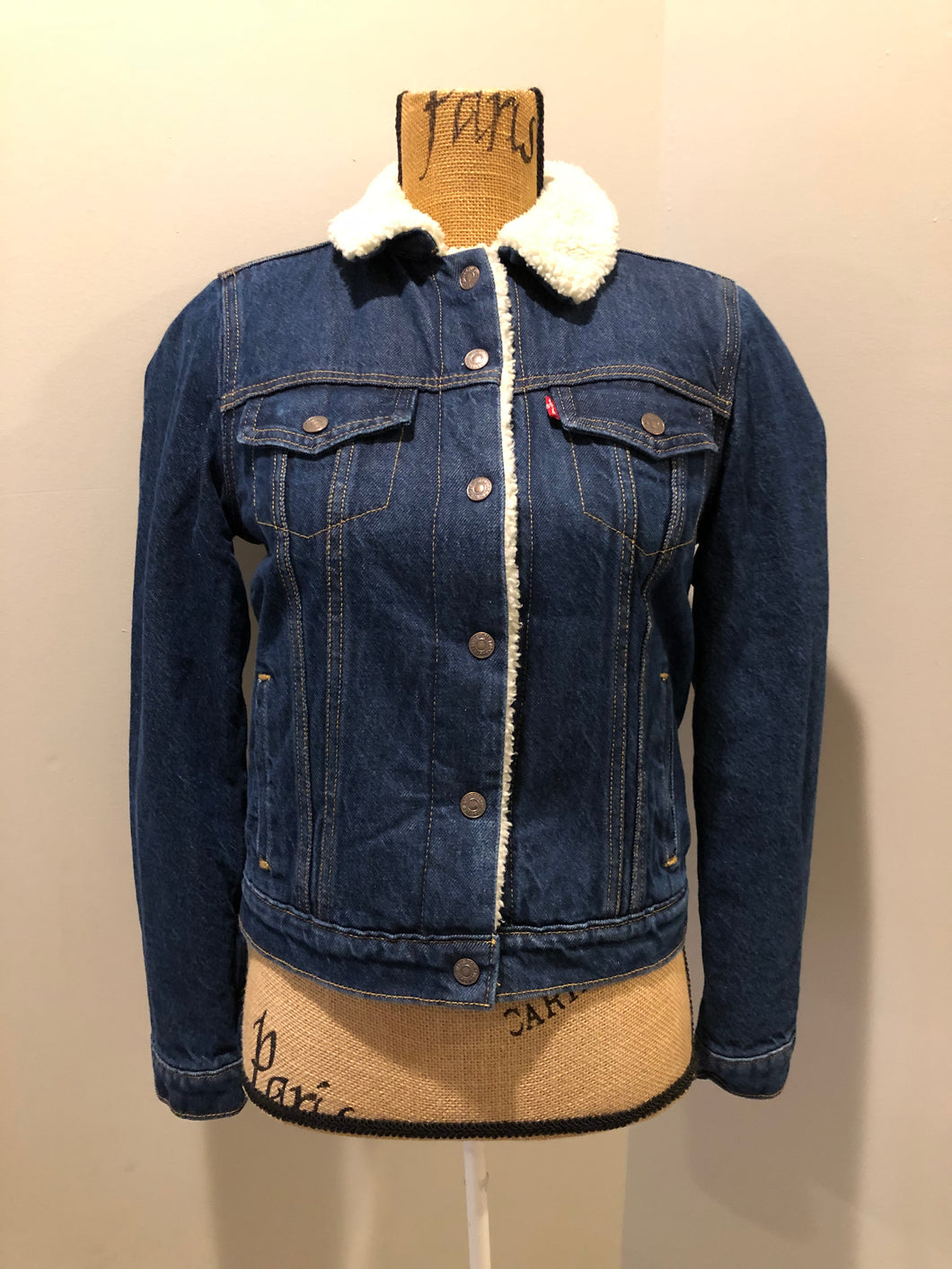 Levi's denim sherpa trucker jacket in a medium wash with faux fur lining, snap closures, vertical pockets and two flap pockets. Size small.