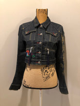 Load image into Gallery viewer, People for Peace cropped denim jacket in a dark wash with colourful embroidery all over, button closures, two zip pockets and two flap pockets on the chest. Size small.