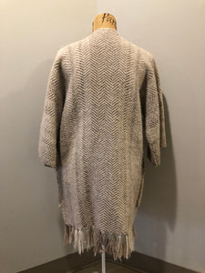 Daurene Lewis 100% wool hand spun, hand woven and hand made cardigan. The cardigan features two lined patch pockets. two wooden button closures at the top and a wool fringe at the bottom. Made in Annapolis Royal, Nova Scotia.