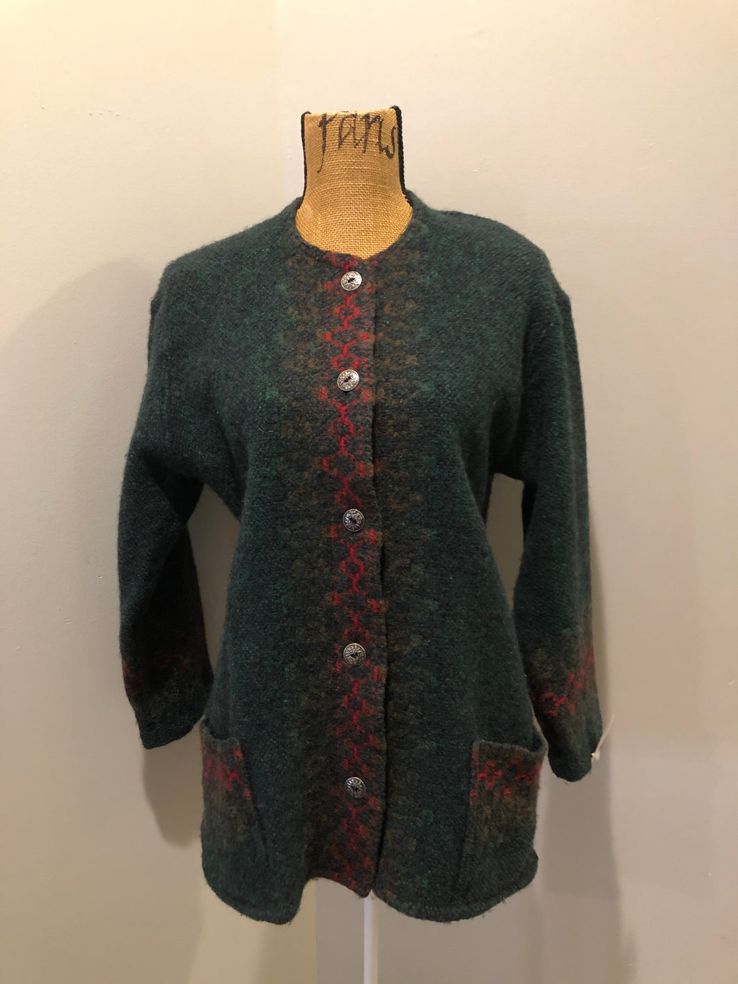 Deweevers wovens 100% wool cardigan in deep green with red design woven in, patch pockets and silver buttons with floral design. Made in Aylesford, NS. Size medium.