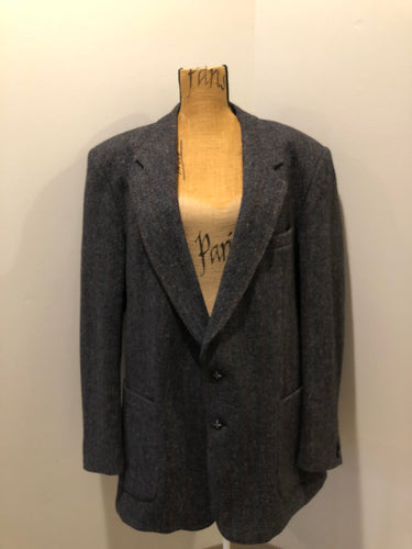 Kingspier Vintage - Harris Tweed grey herringbone with subtle red and blue stripe 100% wool jacket. This jacket is a two button, notch lapel with two patch pockets, a breast pocket and three inside pockets.