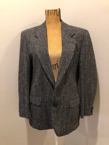 Harris Tweed black and white 100% wool tweed jacket. This jacket is a two button, notch lapel with two flap pockets, a breast pocket and two inside pockets. Made in Canada. Size 40.