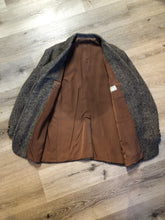 "Load image into Gallery viewer, Donegal handwoven grey with blue and orange flecks 100% wool tweed jacket. This jacket is a two button, notch lapel with two patch pockets, a breast pocket and two inside pockets and a ""this I defend"" emblem embroidered on the chest. Made in Ireland."
