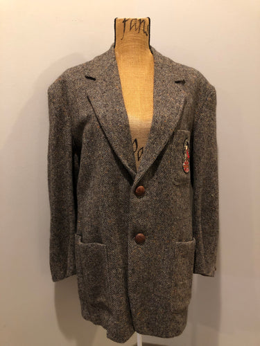 "Kingspier Vintage - Donegal handwoven grey with blue and orange flecks 100% wool tweed jacket. This jacket is a two button, notch lapel with two patch pockets, a breast pocket and two inside pockets and a ""this I defend"" emblem embroidered on the chest. Made in Ireland."