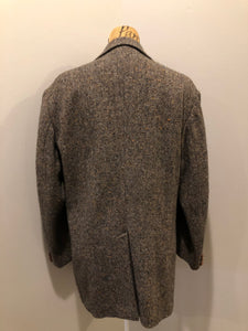 "Donegal handwoven grey with blue and orange flecks 100% wool tweed jacket. This jacket is a two button, notch lapel with two patch pockets, a breast pocket and two inside pockets and a ""this I defend"" emblem embroidered on the chest. Made in Ireland."