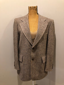 Harris Tweed beige with rust and grey flecks 100% wool tweed jacket. This jacket is a two button, notch lapel with two flap pockets, a breast pocket and two inside pockets. Made in Canada. Size 42R.