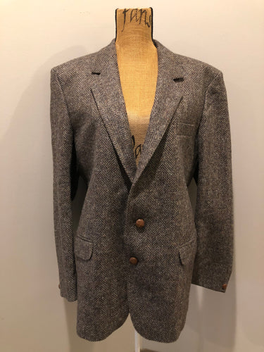 Kingspier Vintage - Paul Henry grey herringbone with flecks blue and rust 100% wool tweed jacket. This jacket is a two button, notch lapel with two flap pockets, a breast pocket and three inside pockets. Made in Europe.