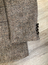 Load image into Gallery viewer, Kingspier Vintage - Harris Tweed beige with rust and grey flecks 100% wool tweed jacket. This jacket is a two button, notch lapel with two flap pockets, a breast pocket and two inside pockets. Made in Canada. Size 42R.