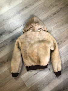 Kingspier Vintage - Ewe Wear, genuine sheepskin hooded bomber style jacket. This jacket features shearling lining, hood, zipper closure and slash pockets. Made in Kingston, Nova Scotia. Size XS.