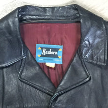 Load image into Gallery viewer, Roxboro Casuals black leather jacket with button closures, zipper, two flap pockets and a red lining.