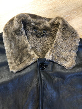 Load image into Gallery viewer, 2dm black sheepskin coat with shearling trim and lining, button closures and slash pockets.