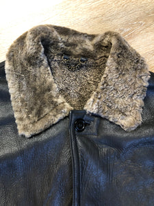 2dm black sheepskin coat with shearling trim and lining, button closures and slash pockets.