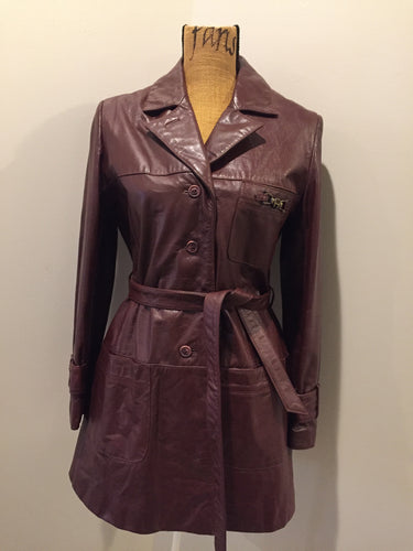 "Kingspier Vintage - Etienne Aguier burgundy leather jacket with button closures, patch pockets, belt and ""A"" decorative details. Size small."