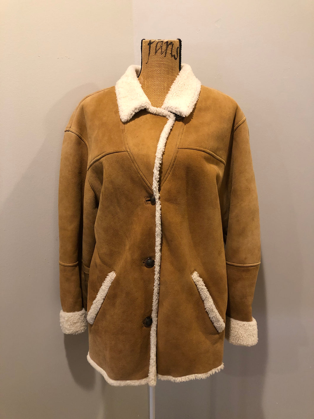 Timberland tan suede lambskin coat with shearling trim and lining, button closures and slash pockets. Coat is water resistant. Size medium.