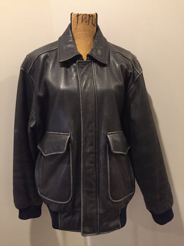 Kingspier Vintage - Black leather pilot jacket with zipper and snap closures, flap pockets, knit trim, inside pocket and plane pattern on inside lining. Size large.