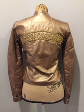 "Load image into Gallery viewer, Rocawear metallic gold leather moto jacket with ""RW"" detail zippers, chain lace-up detail on sides and ""ROCAWEAR"" written in chain across the back. There is a front zipper, two horizontal zip pockets on the chest, two snap closures on the stand up collar and a pocket on the inside. Size small."