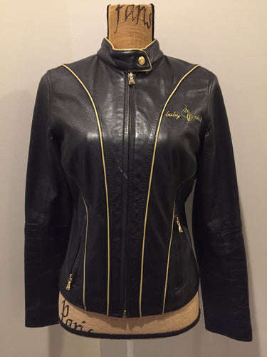 "Kingspier Vintage - Baby Phat black leather moto jacket with gold piping and ""Baby Phat"" embroidered on the chest, front zipper and two vertical zip pockets. A pattern is stitched into the elbows and ""Baby Phat"" is stitched across the back. Size small."