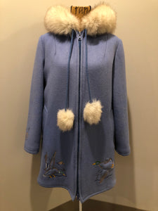 Kingspier Vintage - Northern Sun pure virgin wool northern style parka in light blue. This parka features a hood with white fur trim, zipper closure, quilted lining, slash pockets, hidden inside knit cuffs, embroidered geese design on the front and back and boats embroidered on the sleeves. Made in Canada.