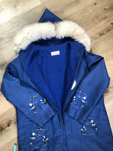Blue northern parka made by Marilyn Bessey with wool blend lining, hood with white fur trim, fur Pom poms, zipper closure, patch pockets, arctic life design embroidered on the front pockets and the sleeves. Made in Canada.