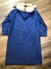 Load image into Gallery viewer, Blue northern parka made by Marilyn Bessey with wool blend lining, hood with white fur trim, fur Pom poms, zipper closure, patch pockets, arctic life design embroidered on the front pockets and the sleeves. Made in Canada.