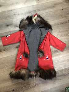 Children's red northern parka featuring a hood, fur trim and pom poms, zipper closure, wool lining, patch pockets, embroidered winter scenes along the front. Made in Canada.