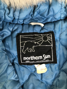 Northern Sun light blue pure virgin wool northern parka featuring a hood with white fur trim, zipper closure, quilted lining, slash pockets, hidden knit cuffs and arctic life design felt appliqué on the front and back. Made in Canada.