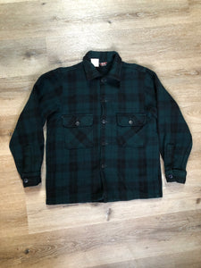 Woolrich dark green plaid wool lumberjack shirt with button closures and two flap pockets on the chest.